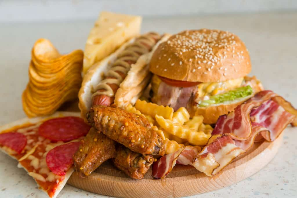 a picture of a hamburger, chicken wings, pizza, potato chips, bacon and a hotdog examples of foods that aren't good to build muscle