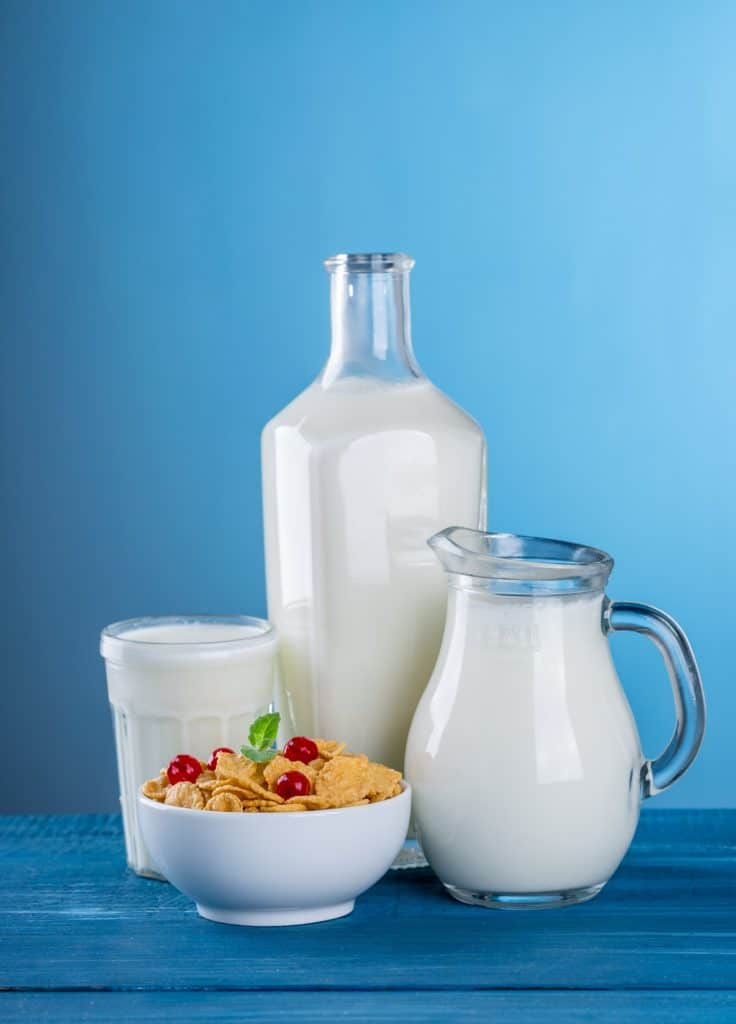 a picture of skim milk in a pitcher and a bowl of dry cereal