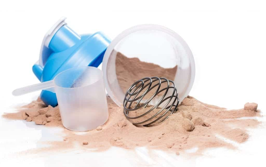 a picture of a shaker bottle fallen over with whey protein powder spilled out