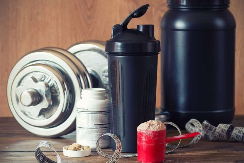 supplement shaker bottles, a bric tape measure and a set of dumbbells