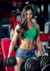 A young fit woman performing a strength training  regimen where she will need to know how to chart weight loss progress