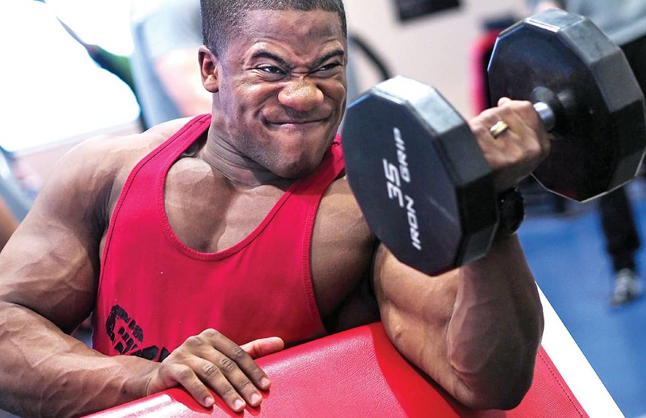 picture of a male bodybuilder doing an intense bicep exercise showing how intensity levels can change your progress results