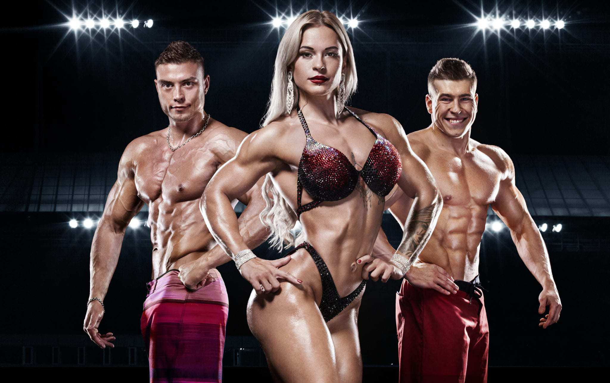 Young strong men and woman bodybuilders on background with lights.