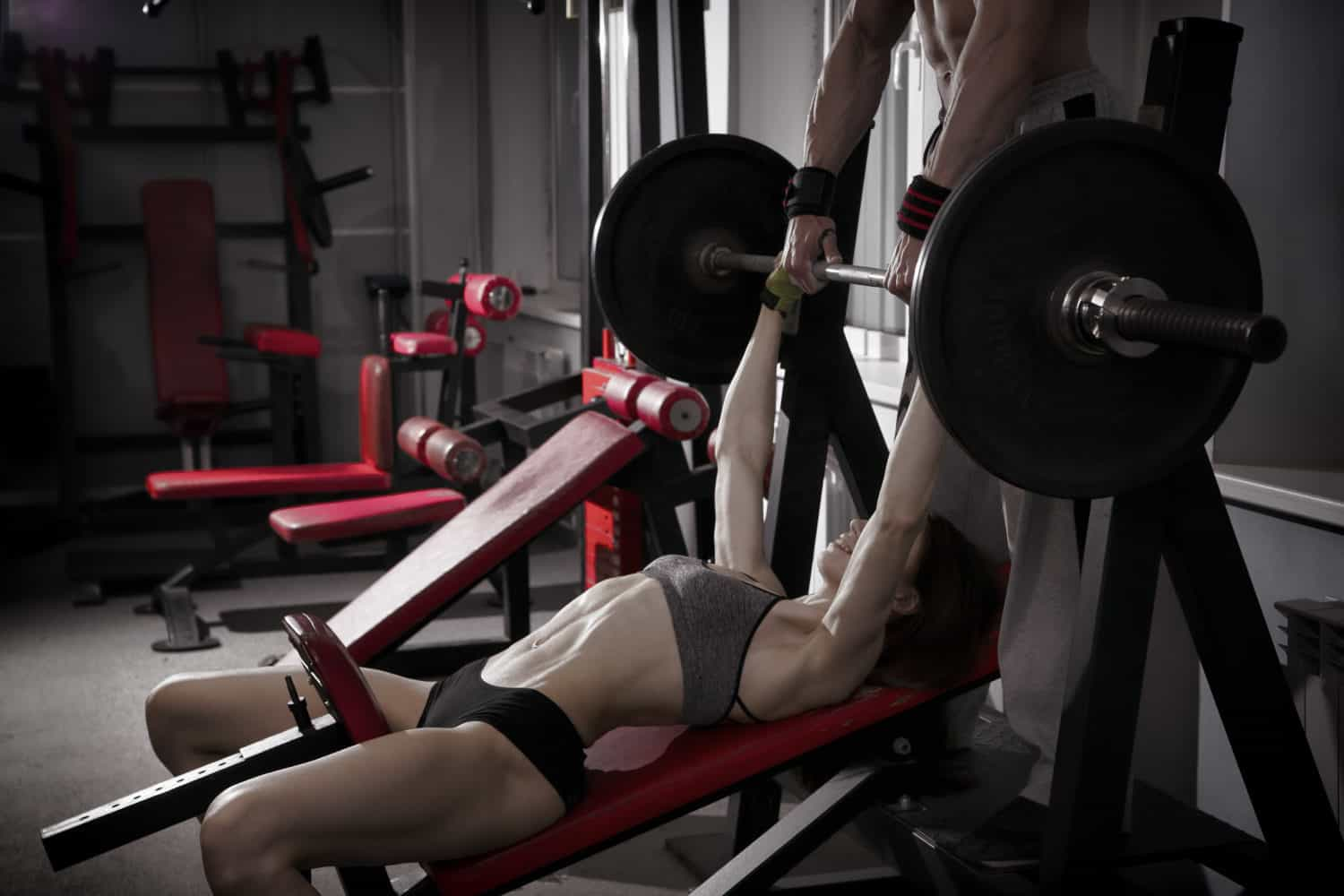 A young woman performing a bench press with bands