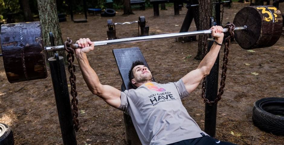 A young man performing a bench press with bands.
