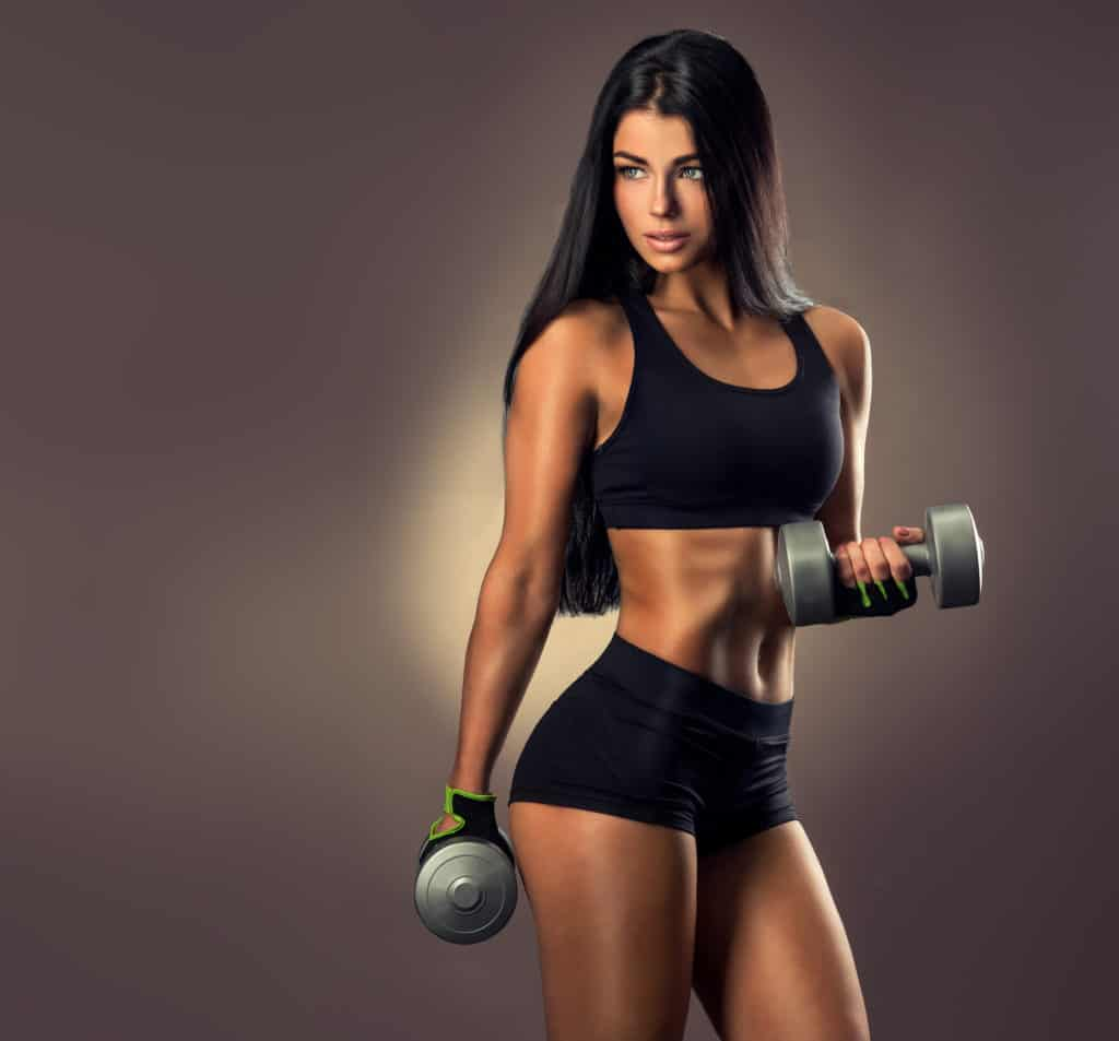 gorgeous brunette doing dumbbell curls as one of the best exercises to lose weight.