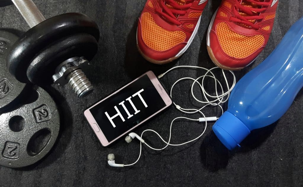 A picture of dumbbells, shoes, water bottle and a phone with HIIT written on it. HIIT stands for HIGH INTENSITY TRAINING