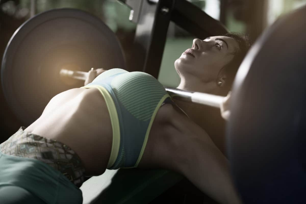 a young woman arching her back during a bench press with bands