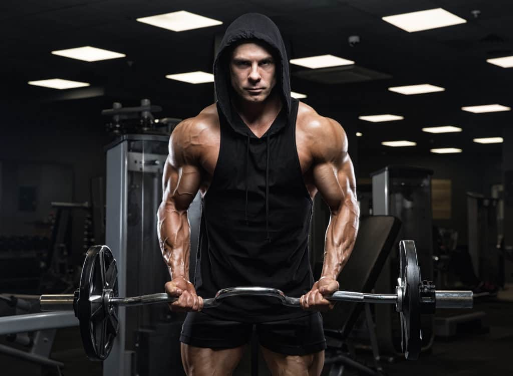 male bodybuilder doing tricep extensions with an EZ curl bar