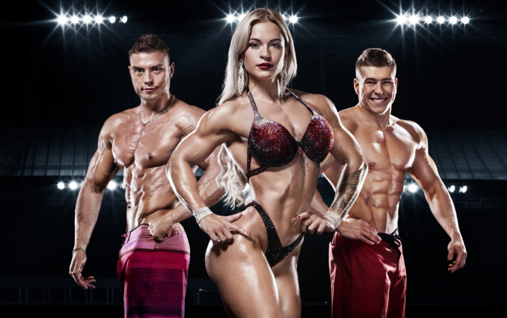 Two male bodybuilders flanking a female bodybuilder, all three have very low body fat