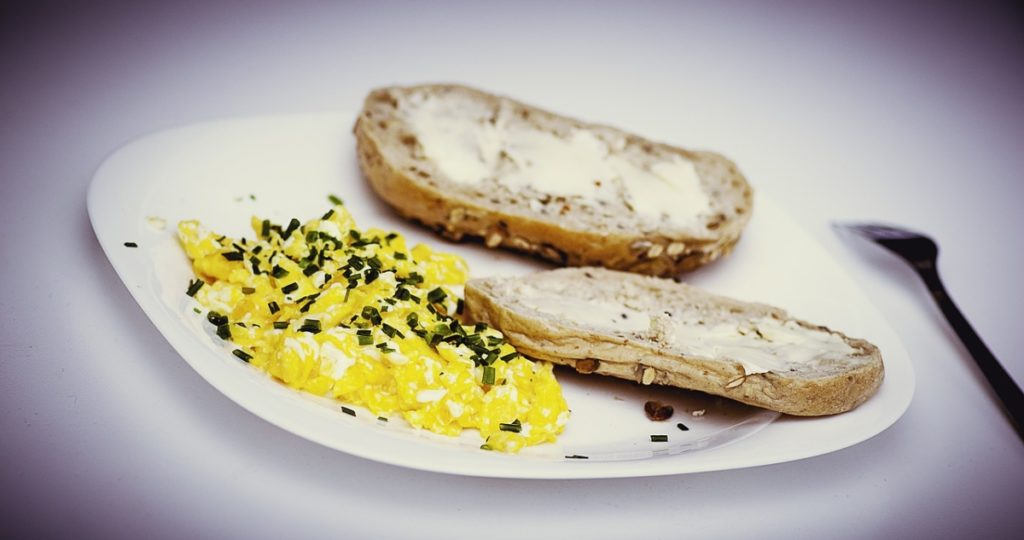 A picture of scrambled eggs and wheat bread, a good source of protein and vitamins for building muscle.