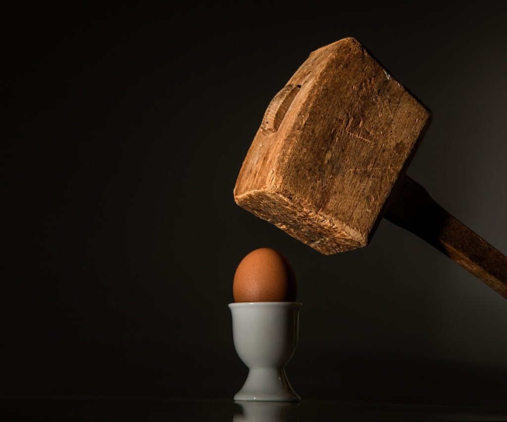 A picture of an egg in an egg holder about to be smashed with a wooden mallet, this is depicting people who don't like eggs in their bodybuilding breakfast.