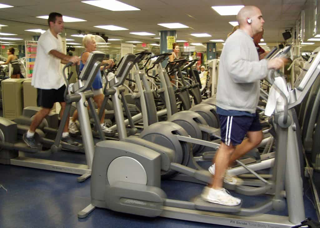 men and women at the gym doing cardio exercises on ellipticals