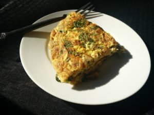 A picture of an omelet made with protein rich eggs and egg whites packed with black beans, shredded cheese, salsa, onions and red peppers for the perfect bodybuilding diet
