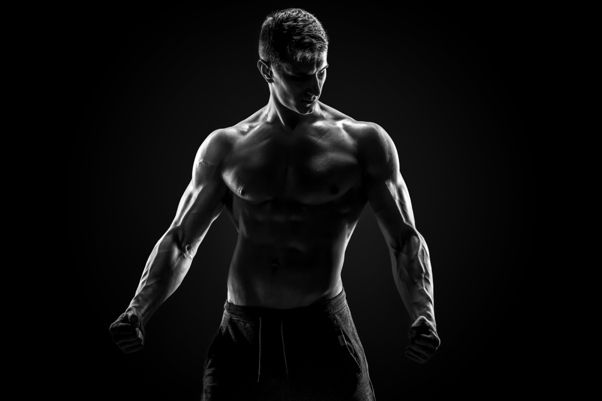 Sexy muscular man posing with naked torso in studio and looking behind on black background. Black and white