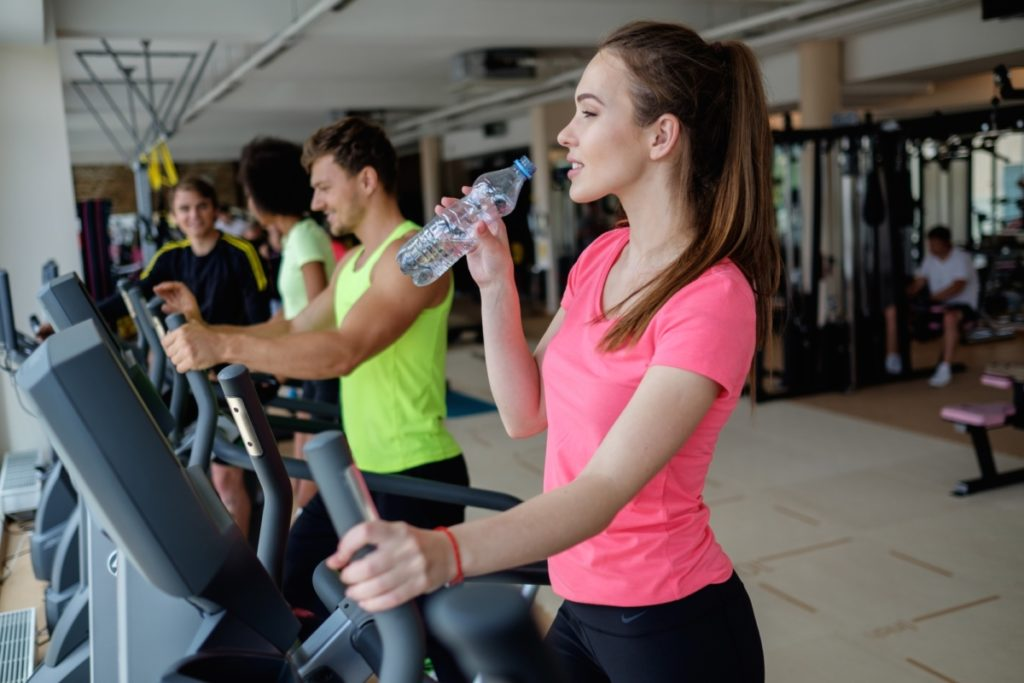 People exercising on a cardio training machines in a gym trying to build muscle after 40