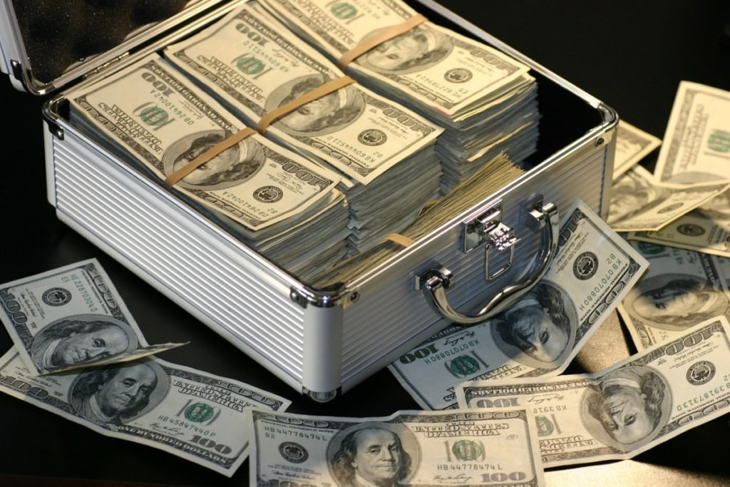 a silver briefcase full of stacks of hundred dollar bills representing how much dicaffeine malate costs