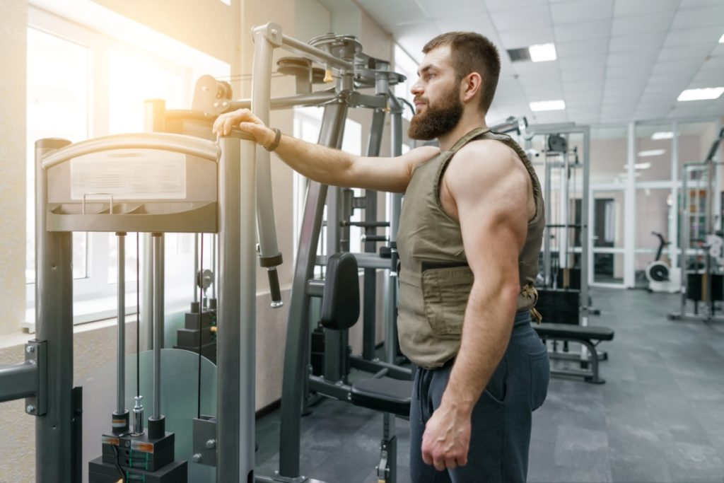 Portrait muscular caucasian bearded man dressed in weighted vest in the gym, military style. understanding what weighted vest benefits are.