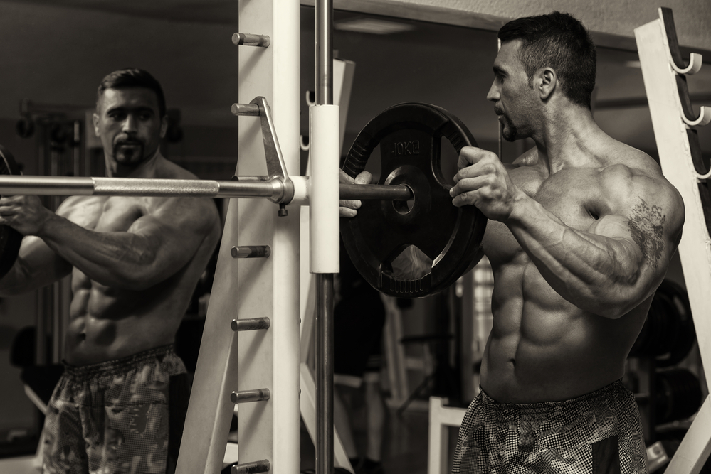Body Builder Putting Weights On Bar In Gym after taking the best legal steroids that work
