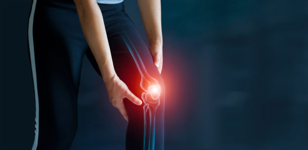 Sport woman suffering from pain in the knee. Tendon problems and Joint inflammation on dark background. Healthcare and medical.