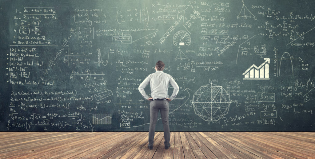 Student studying math on the blackboard full of formulas trying to figure out how many calories should I eat to gain muscle.