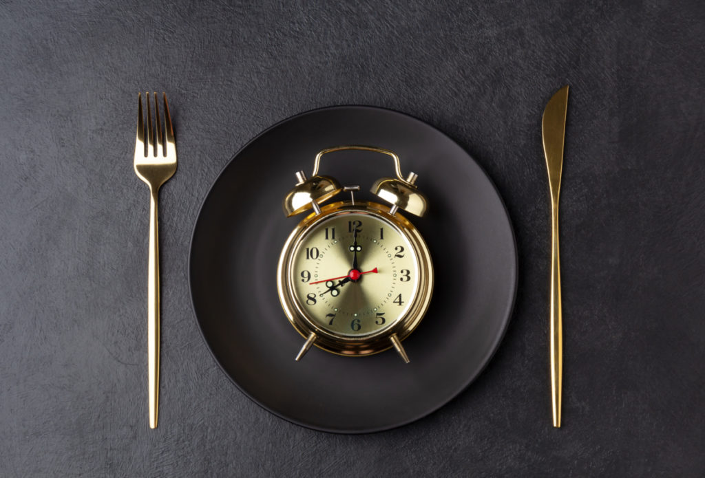Golden alarm clock on a black plate with a golden knife and fork. meal timing for best results at gaining muscle concept. Horizontal orientation, top view.
