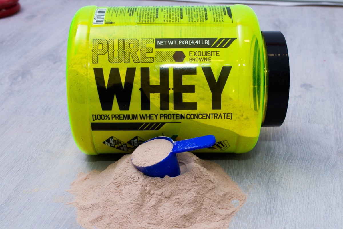 A tub of whey protein concentrate laying on its side with a pile of powder spilled with a blue scoop laying on top