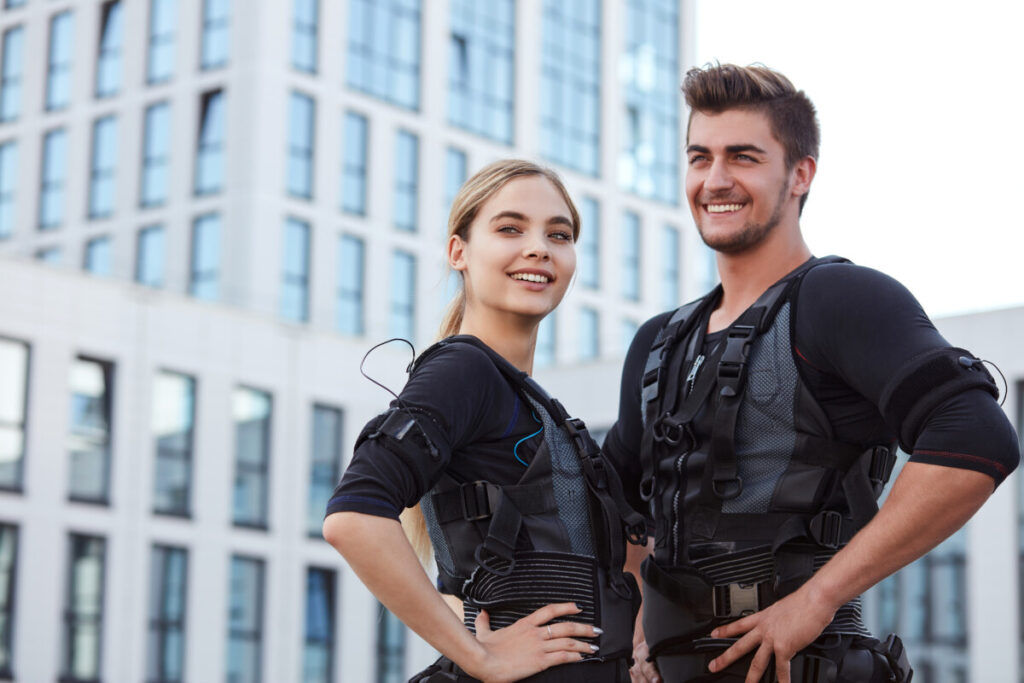 two positive young people wearing fitness vest and posing to the camera on the street.