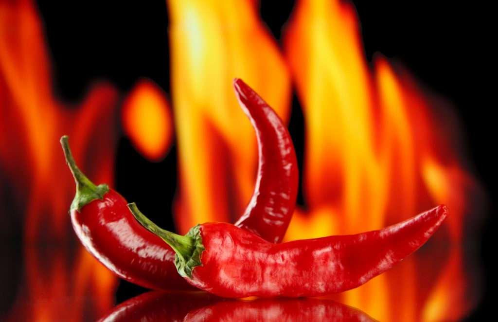 2 chili peppers sitting on a reflective surface with flames in the background as an indication of them being natural thermogenic foods