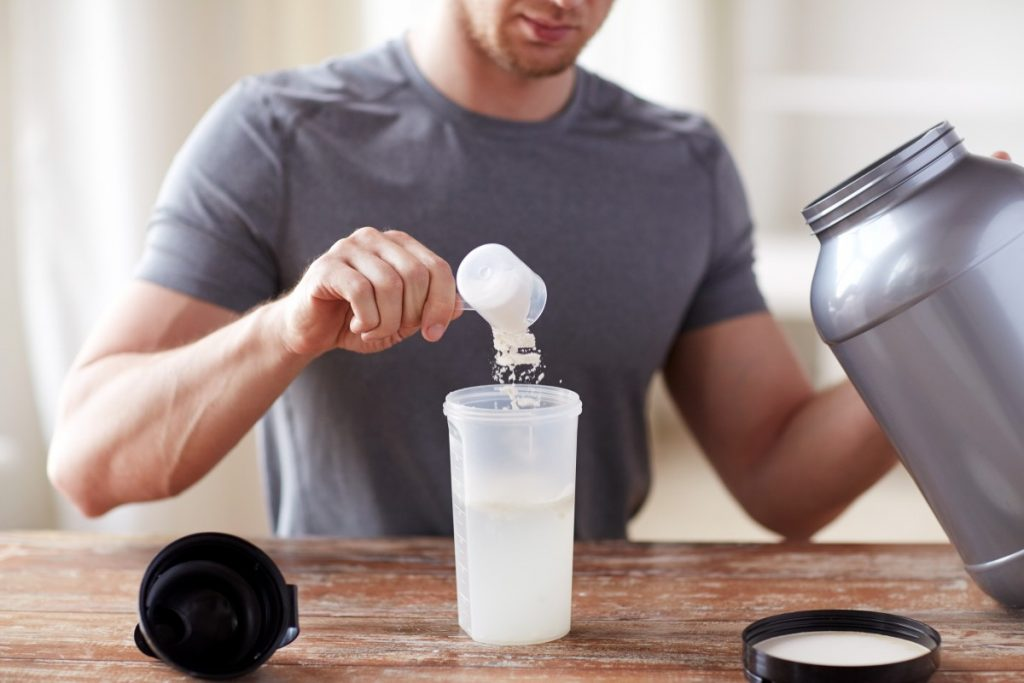 a young male putting the recommended dosage of creatine hcl in his protein shake