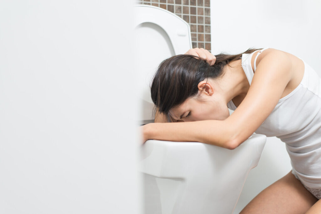 Young woman vomiting into the toilet bowl after taking an expired supplement