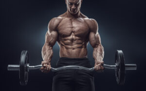 Very muscular male holding a curlbar at mid waste