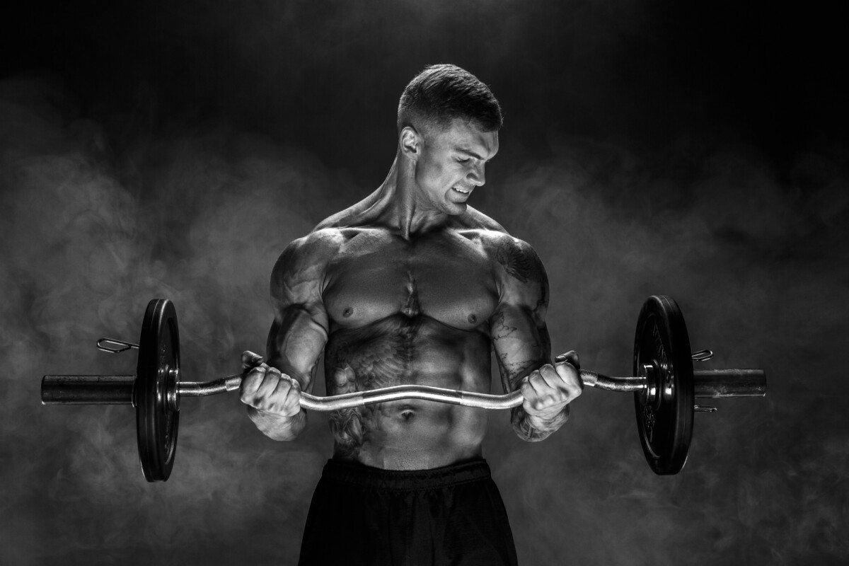 bodybuilder performing biceps exercise with concentrated face over black background with smoke. Using d bal max to raise testosterone