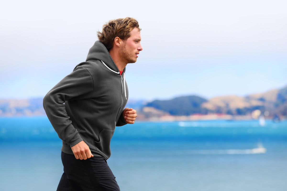 Athlete man running in sweatshirt hoodie in autumn fall by the water. Male runner training outdoors jogging in nature.