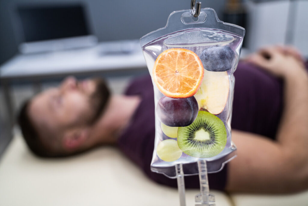 Man In In Hospital Getting IV Infusion but the saline bag has Fruit Slices Inside resembling a IV vitamin therapy