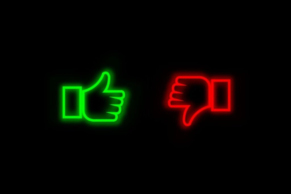 A neon sign with a thumbs up and thumbs down about the pros and cons of Vitamin drips.