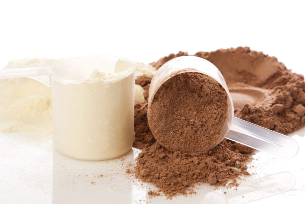 vanilla and chocolate whey protein concentrate powders spilled out on the table.