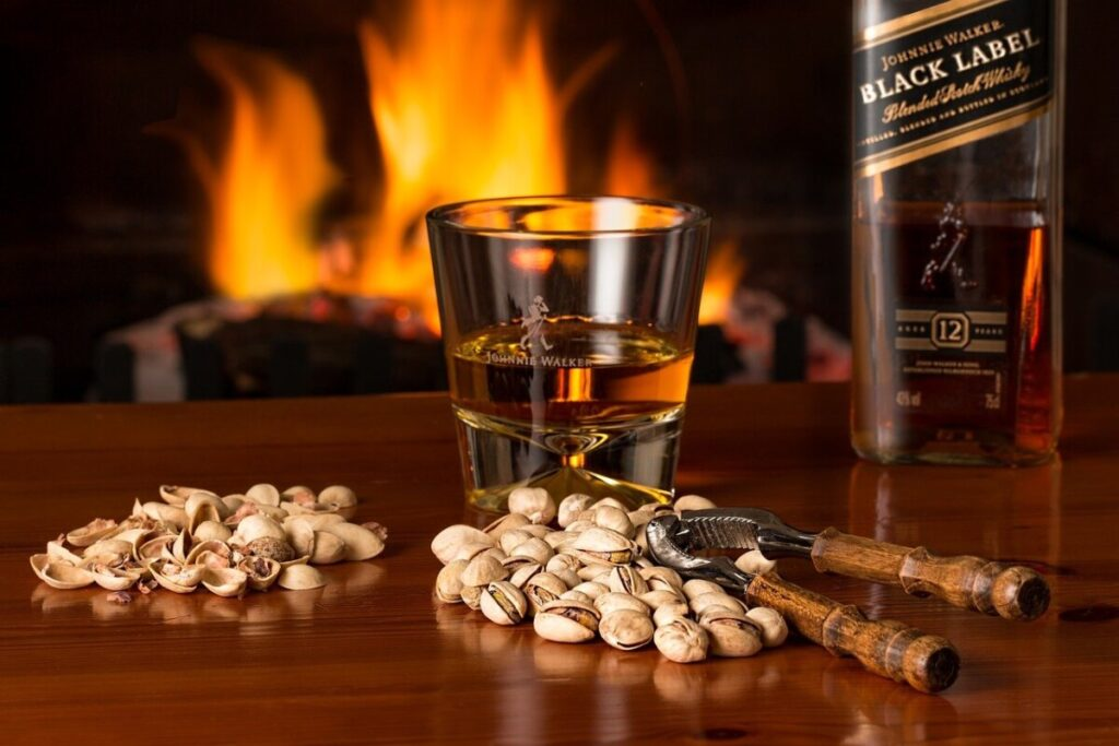a bottle of black label  johnny walker with nuts on a brown table with a fireplace in the back ground