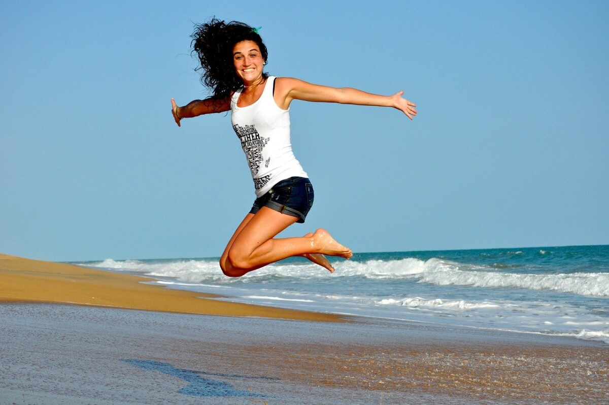 A young woman jumping up and down on the beach