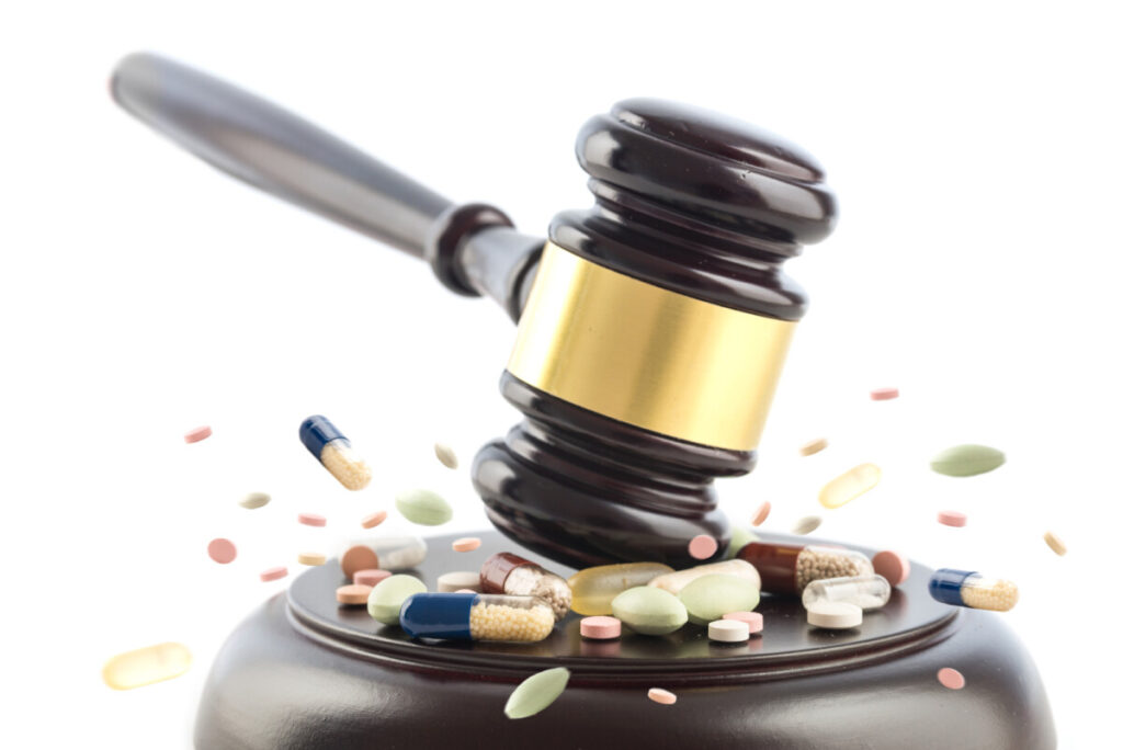 Judge gavel beats on steroid tablets and pills of dianabol,  judge concept, crime with drugs, medicine or doping, isolated on a white background, selected focus, motion blur