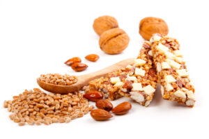 pcture of a home made protein bar a pile of granola and nuts. referrng to when it is the best time to eat a protei bar