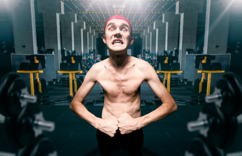 Thin guy poses in gym, skinny dystrophic shows muscle lost after he stopped cycling with dianabol in sport club, funny bodybuilder