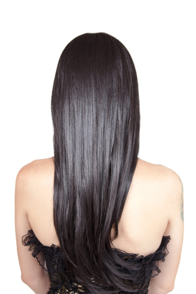 a young woman yturned around showing you her black silky hair that is healthy due to taking vitamins.
