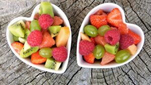 A picture of 2 white bowls shaped like hearts with an assortment of fruits i them to help people with vitamin deficiencies