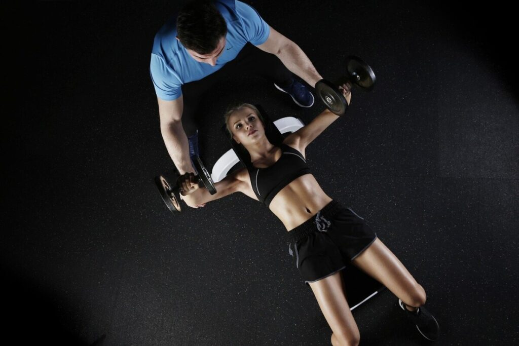 A personal trainer helping a young woman with dumbbell chest presses.
