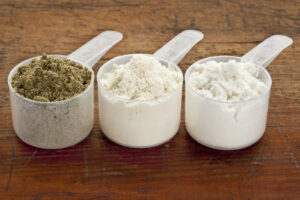 # scoops of protein powder one being soy protein, whey protein and pea protein