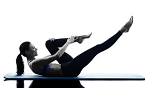 a silhouette of a woman doing pilate exercises on a yoga mat