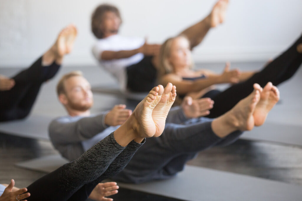 Group of young sporty people practicing yoga lesson with instructor, stretching in Paripurna Navasana exercise, balance pose, working out, indoor close up image, studio, focus on feet.referring to the health benefits of pilates