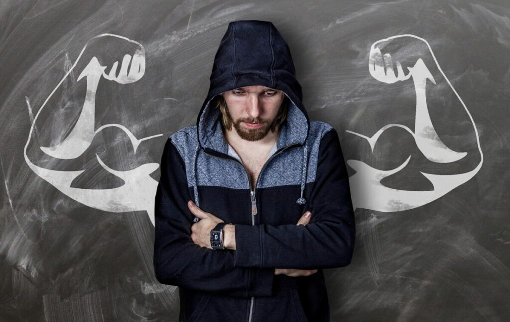 A bodybuilder with his arms crossed standing in front of a chalkboard that has arms drawn on it with huge biceps. Referring to the amount of muscle you'll be able to gain using P var