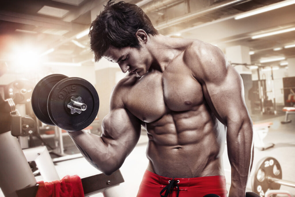 Muscular bodybuilder guy doing exercises with dumbbells in gym after supplementing with D anaoxn a legal steroid alternative